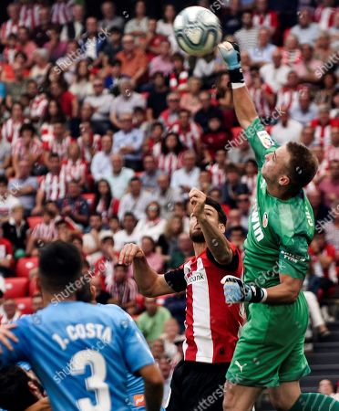 Valencia CF's Dutch goalkeeper Jasper Cilessen (R) clears the ball before Athletic Club Bilbao's striker Aritz Aduriz (C) during their Spanish LaLiga soccer match at San Mames stadium in Bilbao, Spain, 28 September 2019.