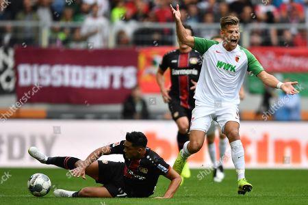 Augsburg's Florian Niederlechner (R) in action against Leverkusen's Isaac Kiese Thelin during the German Bundesliga soccer match between FC Augsburg and Bayer 04 Leverkusen in Augsburg, Germany, 28 September 2019.