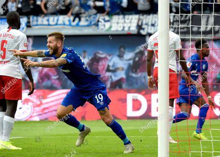 Schalke's Guido Burgstaller, front celebrates the opening goal scored by Schalke's Salif Sane during the German Bundesliga soccer match between RB Leipzig and FC Schalke 04 in Leipzig, Germany