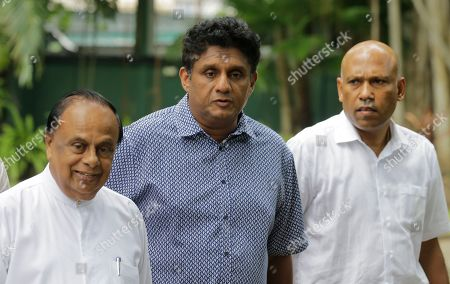 Deputy leader of Sri Lanka's governing United National Party and their presidential candidate Sajith Premadasa, center, arrives for a media briefing with his party men in Colombo, Sri Lanka, . Sri Lanka's governing party on Thursday named Premadasa as its candidate in November's presidential election, ending a long tussle with the party leader, Prime Minister Ranil Wickremesinghe, over the nomination
