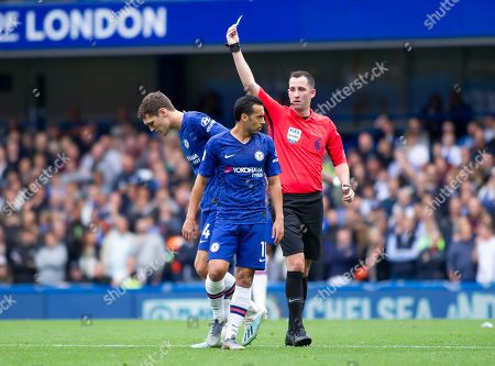 Andreas Christensen of Chelsea receives a yellow card from referee Christopher Cavanagh