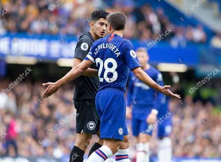 Steven Alzate of Brighton and Hove Albion in discussion with Cesar Azpilicueta of Chelsea after he receives a yellow card from referee Christopher Cavanagh for simulation