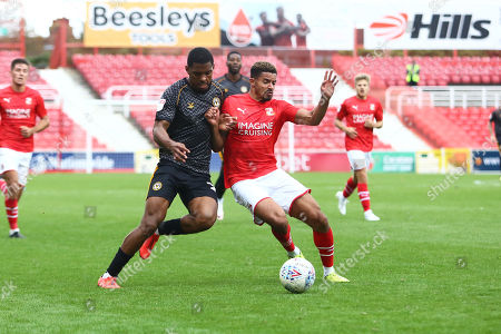 Tristan Abrahams of Newport County and Zeki Fryers of Swindon Town compete for a ball