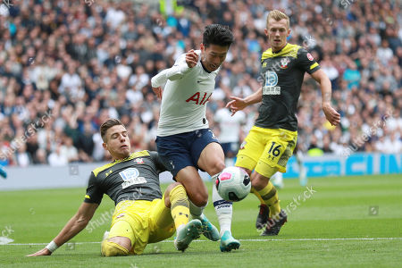 Tottenham's Son Heung-min, center, is tackled by Southampton's Jan Bednarek, left, and Southampton's James Ward-Prowse, right, during the English Premier League soccer match between Tottenham Hotspur and Southampton at the White Heart Lane stadium in London