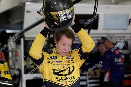 Brad Keselowski puts on his helmet during practice for Sunday's NASCAR Cup Series auto race at Charlotte Motor Speedway in Concord, N.C