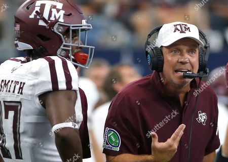 Texas A&M head coach Jimbo Fisher talks with his team as wide receiver Ainias Smith (17) looks on as they play Arkansas during the first half of an NCAA college football game, in Arlington, Texas. Texas A&M won 31-27