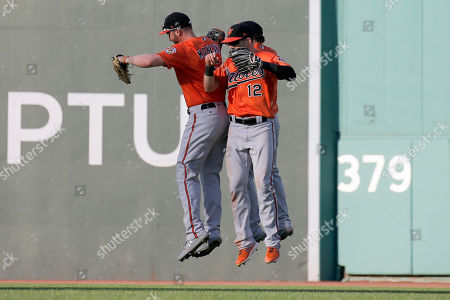 Baltimore Orioles outfielders Trey Mancini, left, Stevie Wilkerson, and Austin Hays (12) celebrate their win over the Boston Red Sox at the end of the baseball game, in Boston