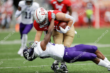 Northwestern defensive back Coco Azema (27) tackles Wisconsin tight end Jake Ferguson (84) during the first half of an NCAA college football game, in Madison, Wis