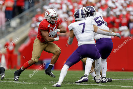 Wisconsin running back Jonathan Taylor (23) runs against Northwestern defensive back Travis Whillock (7) and linebacker Blake Gallagher (51) during the second half of an NCAA college football game, in Madison, Wis. Wisconsin won 24-15