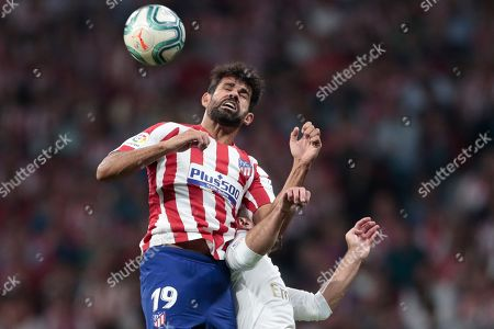 Atletico Madrid's Diego Costa heads the ball as he jumps with Real Madrid's Dani Carvajal during the Spanish La Liga soccer match between Atletico Madrid and Real Madrid at the Wanda Metropolitano stadium in Madrid