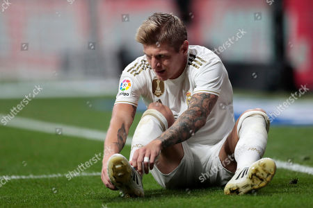 Real Madrid's Toni Kroos adjusts his shoe after a tackle during the Spanish La Liga soccer match between Atletico Madrid and Real Madrid at the Wanda Metropolitano stadium in Madrid