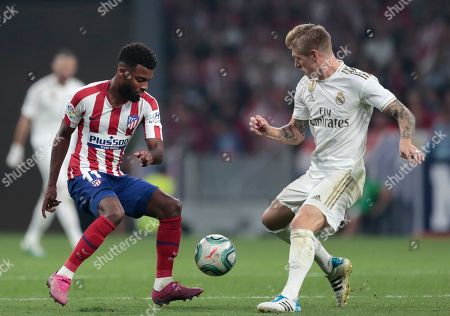 Atletico Madrid's Thomas Lemar, left, and Real Madrid's Toni Kroos vie for the ball during the Spanish La Liga soccer match between Atletico Madrid and Real Madrid at the Wanda Metropolitano stadium in Madrid