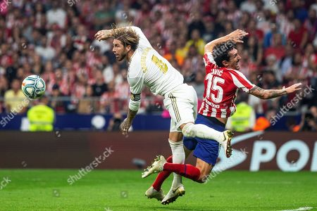 Real Madrid's Sergio Ramos (L) duels for the ball with Atletico Madrid's Stefan Savic during their LaLiga Primera Division soccer match played at the Wanda Metropolitano stadium, in Madrid, Spain, 28 September 2019.