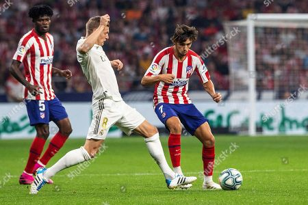 Real Madrid's German midfielder Toni Kroos (C) vies for the ball with Atletico Madrid's Portuguese forward Joao Felix (R) during the LaLiga match between Atletico Madrid and Real Madrid at the Wanda Metropolitano stadium, in Madrid, Spain, 28 September 2019.