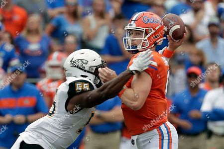 Kyle Trask, Christian Dixon. Florida quarterback Kyle Trask, right, throws a pass as he is hit by Towson linebacker Christian Dixon (55) during the first half of an NCAA college football game, in Gainesville, Fla