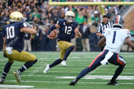 Notre Dame quarterback Ian Book (12) runs with the ball in front of Virginia cornerback Nick Grant (1) in the first half of an NCAA college football game in South Bend, Ind
