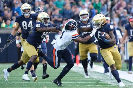 Notre Dame running back Tony Jones Jr. (6) fends off Virginia cornerback Nick Grant (1) in the second half of an NCAA college football game in South Bend, Ind., . Notre Dame won 35-20