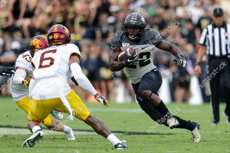 Stock Image of Chris Williamson, King Doerue. Purdue running back King Doerue (22) cuts away from Minnesota defensive back Chris Williamson (6) during the first half of an NCAA college football game in West Lafayette, Ind