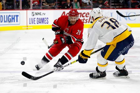 Brian Gibbons, Jeremy Davies. Carolina Hurricanes' Brian Gibbons (29) clears the puck around Nashville Predators Jeremy Davies (38) during the second period of an NHL preseason hockey game, in Raleigh, N.C