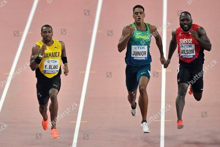 Yohan Blake, of Jamaica, Aldemir Junior, of Brazil, and Alex Wilson, of Switzerland, from left to right, compete in the men's 200 meter heats during the World Athletics Championships in Doha, Qatar