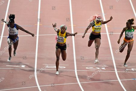 Silver medalist Dina Asher-Smith, of Great Britain, gold medalist Shelly-Ann Fraser-Pryce, of Jamaica, fourth placed Elaine Thompson, of Jamaica, and bronze medalist Marie-Josée Ta Lou, of The Ivory Coast, from left to right, cross the finish line in the women's 100 meter final during the World Athletics Championships in Doha, Qatar
