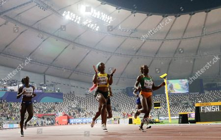 Shelly-Ann Fraser-Pryce, of Jamaica, center, wins the gold medal in the women's 100 meter final ahead of Dina Asher-Smith, of Great Britain, left, silver, at the World Athletics Championships in Doha, Qatar