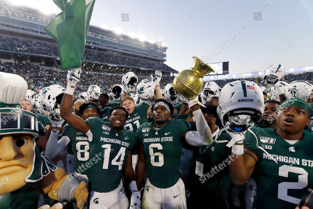 Michigan State players, including Davion Williams (14), David Dowell (6) and Julian Barnett (2), celebrate following a win over Indiana in an NCAA college football game, in East Lansing, Mich