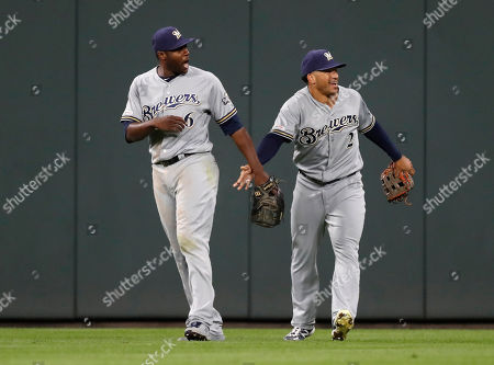 R m. Milwaukee Brewers right fielder Trent Grisham, right, congratulates center fielder Lorenzo Cain after his catch robbed Colorado Rockies' Garrett Hampson of a two-run home run in the seventh inning of a baseball game, in Denver