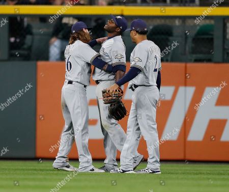 R m. Milwaukee Brewers left fielder Ben Gamel, left, and right fielder Trent Grisham, right, congratulate center fielder Lorenzo Cain after his catch robbed Colorado Rockies' Garrett Hampson of a two-run home run in the seventh inning of a baseball game, in Denver