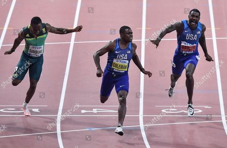 Christian Coleman, of the United States, center, reacts after winning the men's 100 meter race beside fourth placed Akani Simbine of South Africa, left, and second placed Justin Gatlin of the USA, right, during the World Athletics Championships in Doha, Qatar