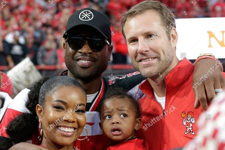 Stock Photo of Nebraska NCAA college basketball coach Fred Hoiberg, right, poses with Gabrielle Union, her husband Dwyane Wade and their daughter Kaavia James Union Wade, during a break in a football game between Nebraska and Ohio State, in Lincoln, Neb