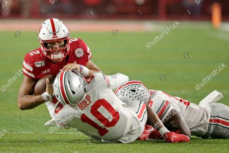 Nebraska quarterback Adrian Martinez (2) is tackled by Ohio State cornerback Amir Riep (10) and linebacker Dallas Gant, right, during the second half of an NCAA college football game in Lincoln, Neb., . Ohio State won 48-7