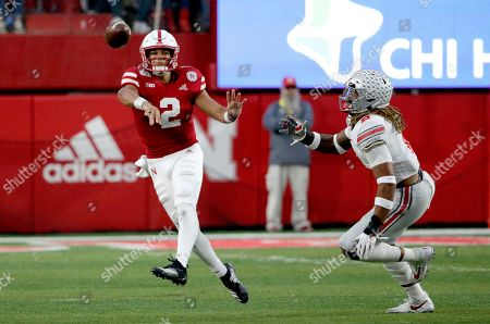Adrian Martinez, Chase Young. Nebraska quarterback Adrian Martinez (2) throws an interception while being pursued by Ohio State defensive end Chase Young, right, during the first half of an NCAA college football game in Lincoln, Neb