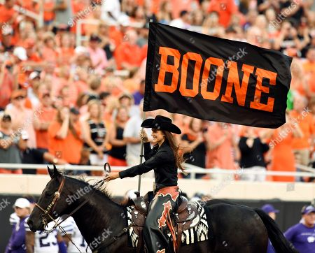 The Oklahoma State spirit rider holds up a banner honoring T. Boone Pickens, following an Oklahoma State touchdown against Kansas State during the first half of an NCAA college football game in Stillwater, Okla., . Pickens, a major donor for the university, died Sept. 11 at the age of 91. Oklahoma State's Boone Pickens Stadium is named after him