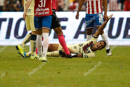 America's Giovani Dos Santos, center, grimaces in pain after a tackle by Guadalajara's Antonio Briseno during a Mexican soccer league match at Azteca stadium in Mexico City