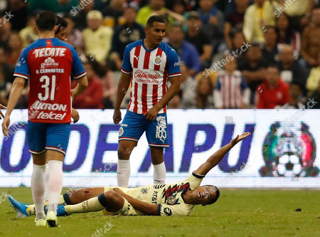 America's Giovani Dos Santos, below, grimaces in pain after a tackle by Guadalajara's Antonio Briseno during a Mexican soccer league match at Azteca stadium in Mexico City
