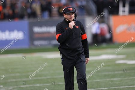 Oregon State head coach Jonathan Smith talks on his headset during the second half of an NCAA college football game against Stanford in Corvallis, Ore., . Stanford won 31-28