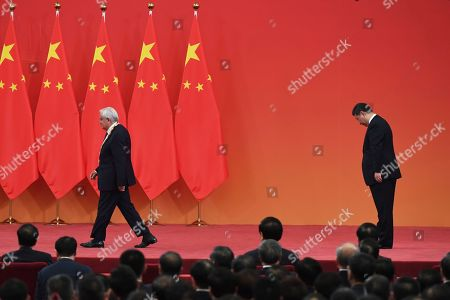 Former French Prime Minister Jean-Pierre Raffarin, left, leaves the stage after receiving an award from Chinese President Xi Jinping at a ceremony in Beijing's Great Hall of the People