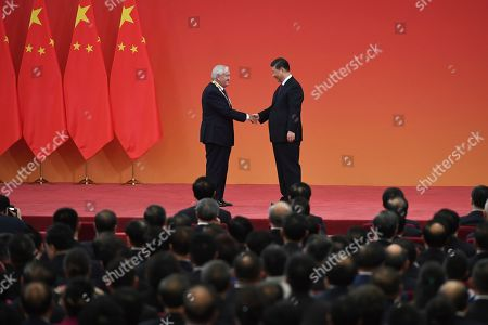 Chinese President Xi Jinping, right, shakes hands with former French Prime Minister Jean-Pierre Raffarin at a ceremony in Beijing's Great Hall of the People