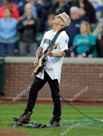 Mike McCready of the rock band Pearl Jam plays the National Anthem before a baseball game between the Seattle Mariners and the Oakland Athletics, in Seattle