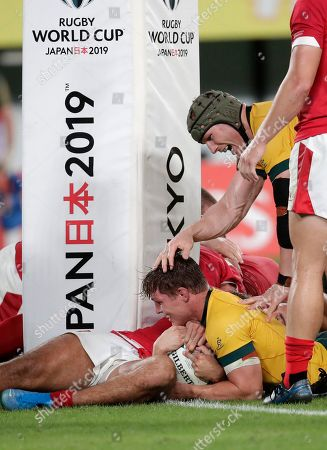 Australia's Michael Hooper is congratulated by teammate David Pocock after scoring a try during the Rugby World Cup Pool D game at Tokyo Stadium between Australia and Wales in Tokyo, Japan