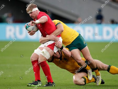 Wales Aaron Wainwright, left, is tackled by Australia's David Pocock and James O'Connor, right, during the Rugby World Cup Pool D game at Tokyo Stadium between Australia and Wales in Tokyo, Japan