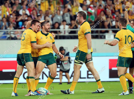 Australia's Adam Ashley-Cooper, third right, celebrates after scoring a try during the Rugby World Cup Pool D game at Tokyo Stadium between Australia and Wales in Tokyo, Japan
