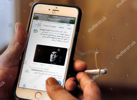 A man reads Saudi news on Twitter fronted by a picture of the prominent bodyguard to Saudi Arabia's King Salman Maj. Gen. Abdulaziz al-Fagham, at a coffee shop, in Jiddah, Saudi Arabia, . Saudi state television reported that al-Fagham has been shot and killed in what authorities describe as a personal dispute in the Red Sea city of Jiddah