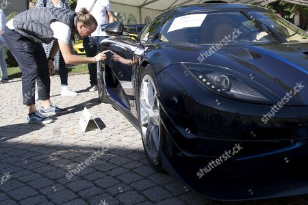 People looking at a 2015 Koenigsegg One:1 model car, part of some 25 luxury cars owned by Teodoro Obiang, the son of the Equatorial Guinea's President Teodoro Obiang Nguema Mbasogo before an auction of sales house Bonhams at the Bonmont Abbey Golf & Country Club in Cheserex near Geneva, Switzerland, 29 September 2019. A collection of luxury cars from Equatorial Guinea's vice president Teodorin Obiang Nguema confiscated by the Geneva prosecutor's office after a deal ending a money-laundering inquiry, are auctioned off in Switzerland and are estimated to bring in 18.5 million Swiss francs.