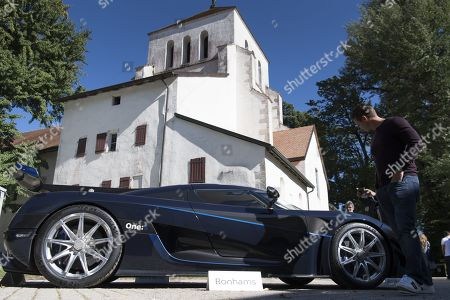 People looking at a 2015 Koenigsegg One:1 model car part of some 25 luxury cars owned by Teodoro Obiang, the son of the Equatorial Guinea's President Teodoro Obiang Nguema Mbasogo before an auction of sales house Bonhams at the Bonmont Abbey Golf & Country Club in Cheserex near Geneva, Switzerland, 29 September 2019. A collection of luxury cars from Equatorial Guinea's vice president Teodorin Obiang Nguema confiscated by the Geneva prosecutor's office after a deal ending a money-laundering inquiry, are auctioned off in Switzerland and are estimated to bring in 18.5 million Swiss francs.