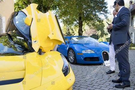 People inspecting a Ferrari LaFerrari (2015), left, and a Bugatti Veyron EB 16.4 Coupe (2010), right, part of some 25 luxury cars owned by Teodoro Obiang, the son of the Equatorial Guinea's President Teodoro Obiang Nguema Mbasogo before an auction of sales house Bonhams at the Bonmont Abbey Golf & Country Club in Cheserex near Geneva, Switzerland, 29 September 2019. A collection of luxury cars from Equatorial Guinea's vice president Teodorin Obiang Nguema confiscated by the Geneva prosecutor's office after a deal ending a money-laundering inquiry, are auctioned off in Switzerland and are estimated to bring in 18.5 million Swiss francs.