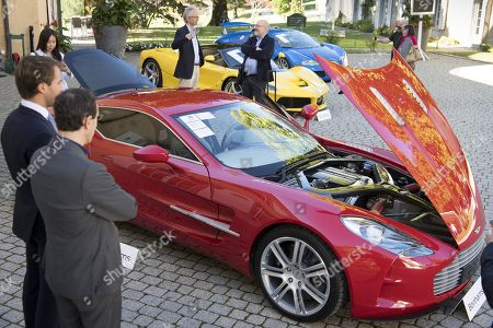 People looking at a Aston Martin One-77 Coupe (2011) in front of a Ferrari LaFerrari (2015), yellow, and a Bugatti Veyron EB 16.4 Coupe (2010), blue, part of some 25 luxury cars owned by Teodoro Obiang, the son of the Equatorial Guinea's President Teodoro Obiang Nguema Mbasogo before an auction of sales house Bonhams at the Bonmont Abbey Golf & Country Club in Cheserex near Geneva, Switzerland, 29 September 2019. A collection of luxury cars from Equatorial Guinea's vice president Teodorin Obiang Nguema confiscated by the Geneva prosecutor's office after a deal ending a money-laundering inquiry, are auctioned off in Switzerland and are estimated to bring in 18.5 million Swiss francs.