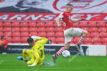 Barnsley midfielder Luke Thomas (16) gets past Brentford goalkeeper David Raya (1) during the EFL Sky Bet Championship match between Barnsley and Brentford at Oakwell, Barnsley