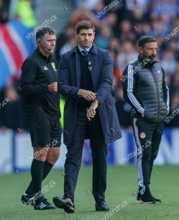 Stock Photo of Rangers Manager Steven Gerrard, with Fourth Official John McKendrick (left) & Aberdeen Manager Derek McInnes (right) during the Ladbrokes Scottish Premiership match between Rangers & Aberdeen at Ibrox Stadium, Glasgow on 28 Sept 2019.